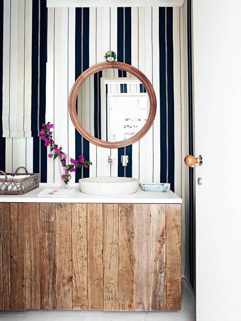 Decoração com armário rústico e espelho redondo.