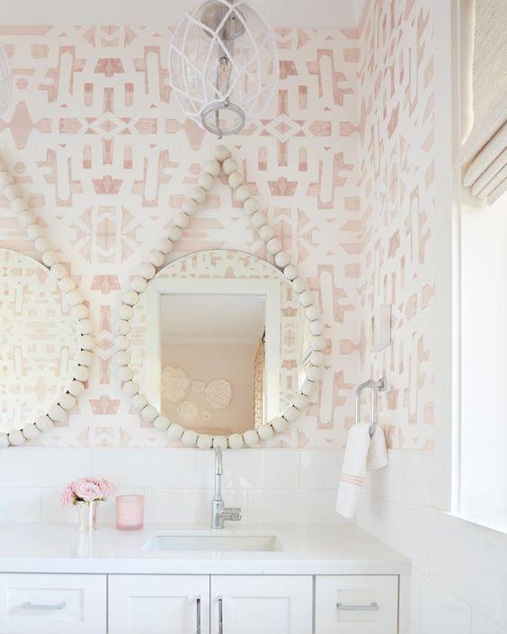 Decoração moderna com armários brancos e espelhos redondos.