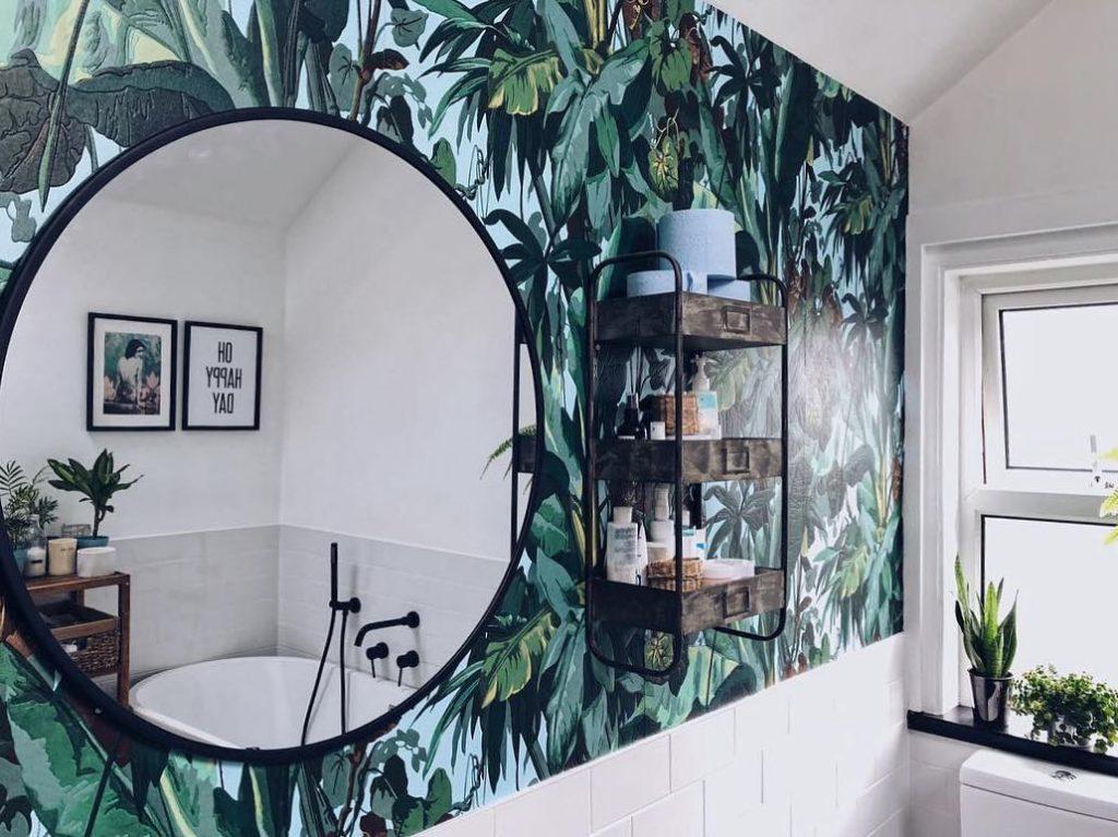 Decoração com estampa de folhas e espelho redondo.
