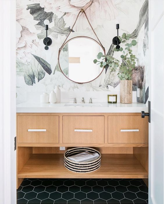 Decoração moderna com estampa floral e espelho redondo.