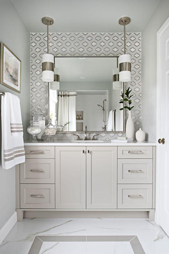 Decoração luxuosa com armário cinza e estampa prateada.
