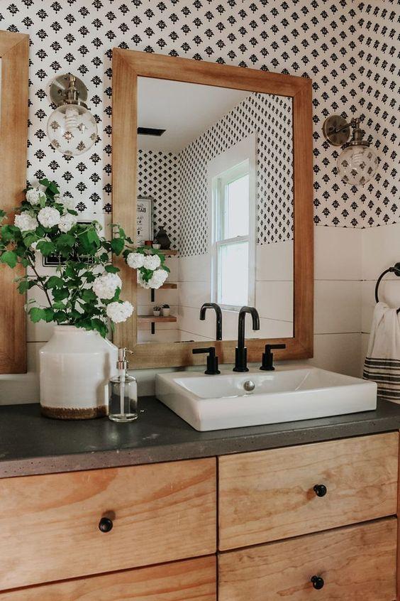 Decoração com armário de madeira e estampa minimalista.