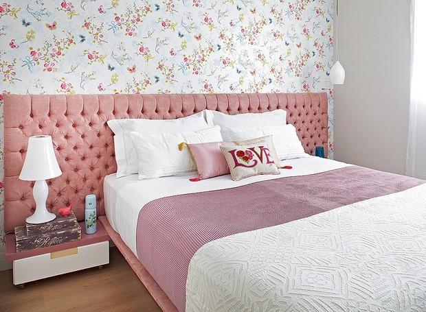 Cômodo com decoração feminina e cabeceira estofada rosa.
