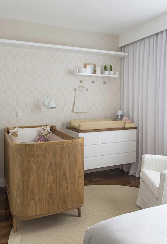 Decoração minimalista com berço moderno e revestimento com estampa simples.