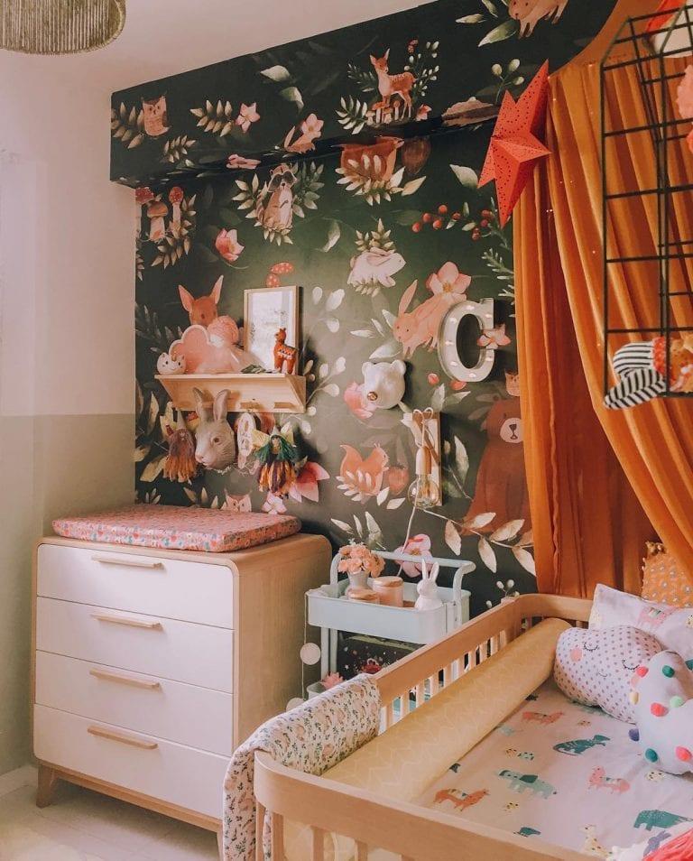 Decoração moderna com berço de madeira e revestimento com estampa com coelhos e ursos.