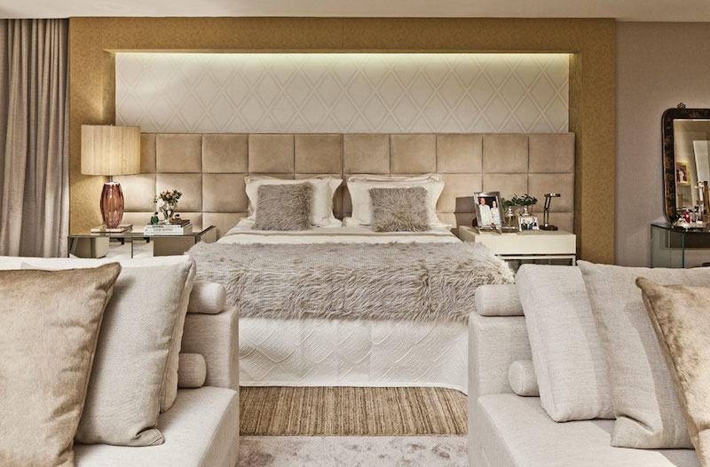 Decoração luxuosa e neutra com cabeceira da cama estofada.