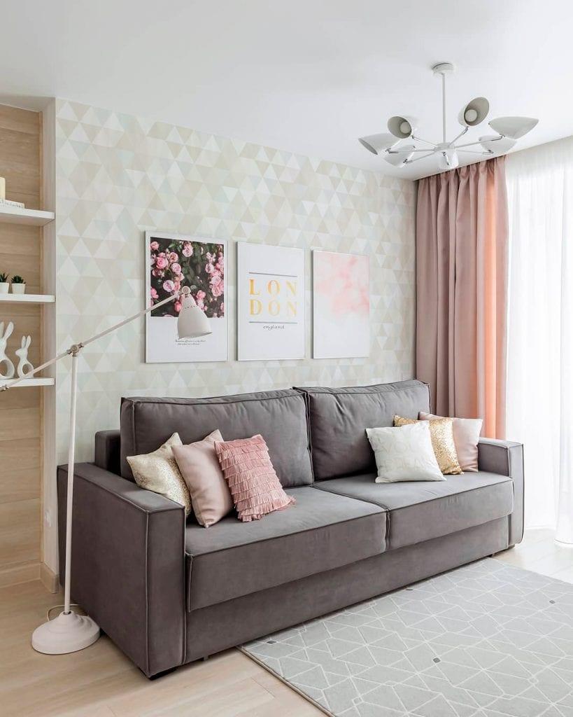 Decoração simples com sofá cinza com parede geométrica.