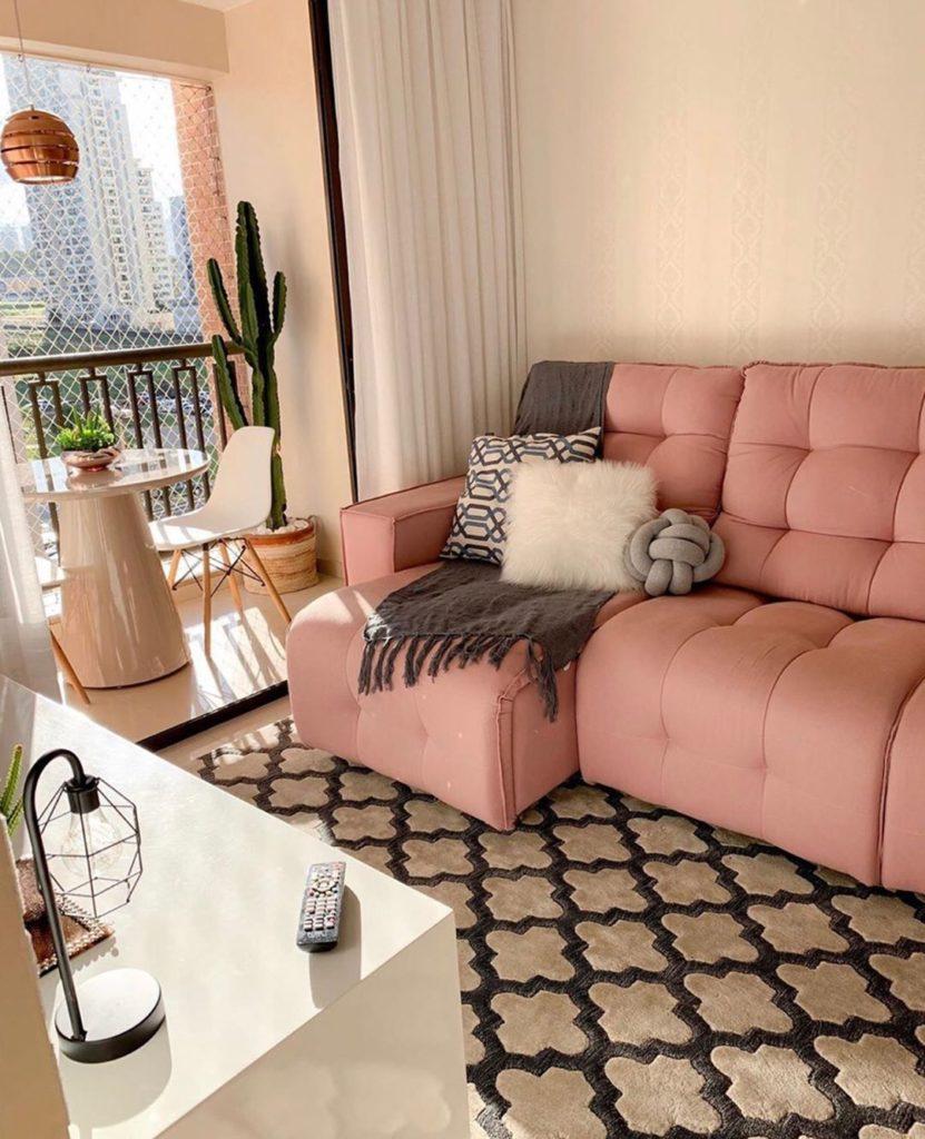 Decoração com sofá rosa com parede com estampa neutra.