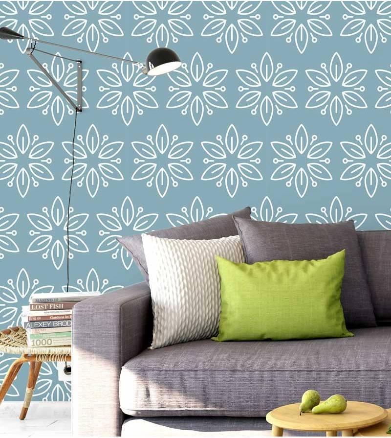 Decoração com sofá cinza e parede com estampa azul.