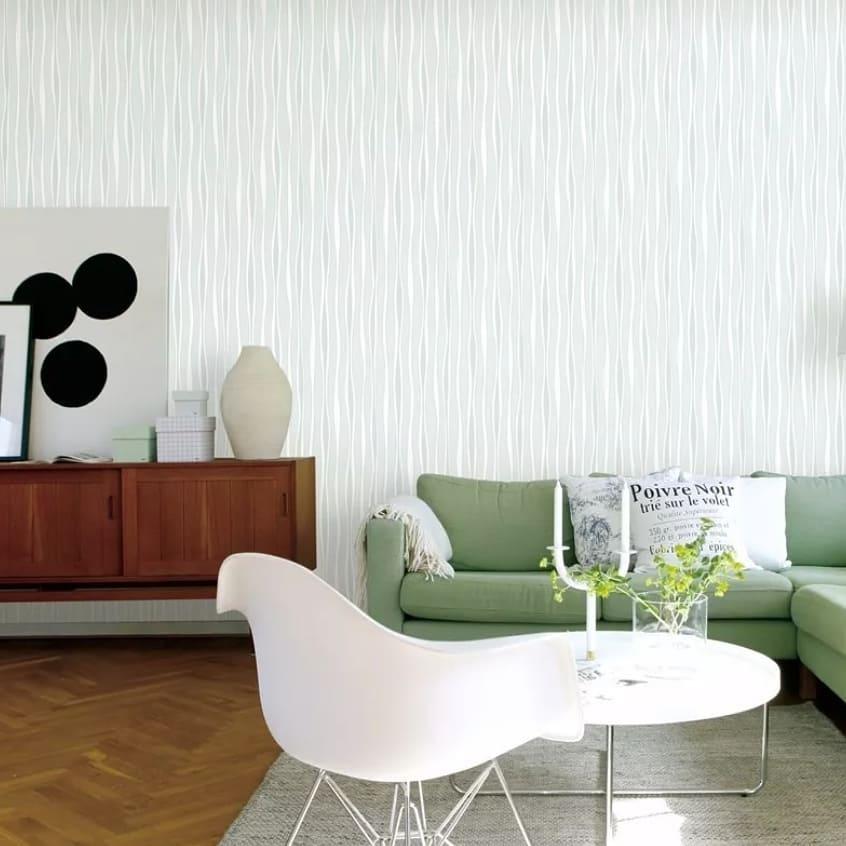 Decoração com sofá verde e parede branca.