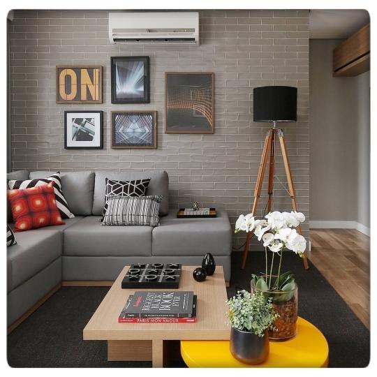 Decoração moderna com parede de tijolinho cinza.