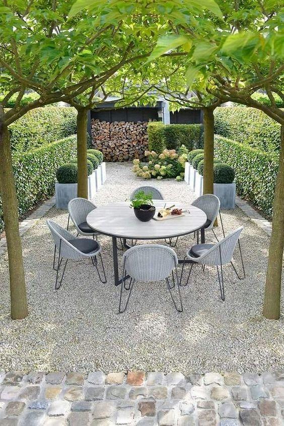 Quintal com árvores que cobrem a mesa.