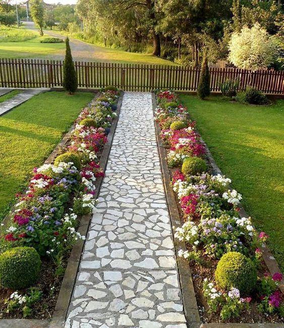 Caminho de entrada na casa com plantas baixas para jardim.