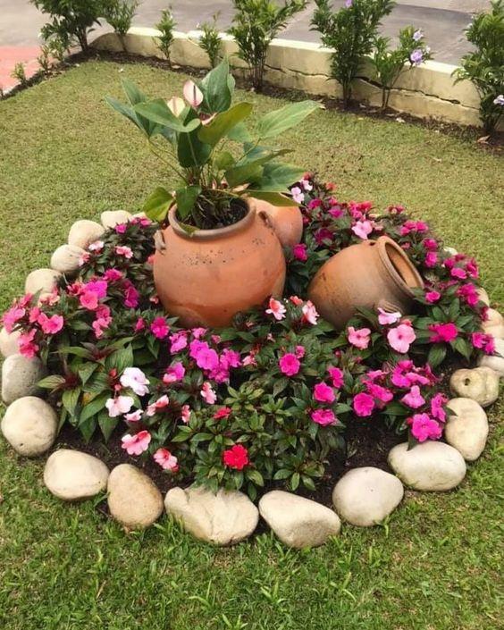 Gramado com um um círculo cheio de flores.