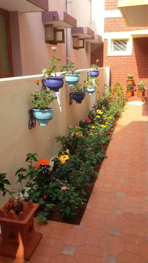 Jardim estreito e cumprido com flores coloridas.