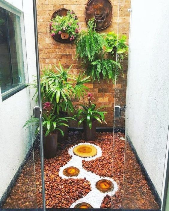 Jardim com plantas em vasos e chão com pedras.