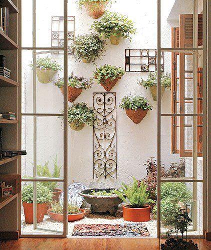 Jardim de inverno com vasos de plantas.