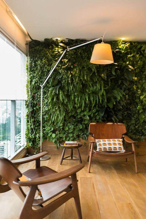 Área com jardim vertical e duas cadeiras.