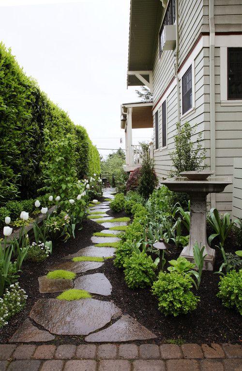 Corredor lateral da casa com jardim.