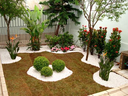 Jardim com grama, pedras brancas e vários tipos de plantas.
