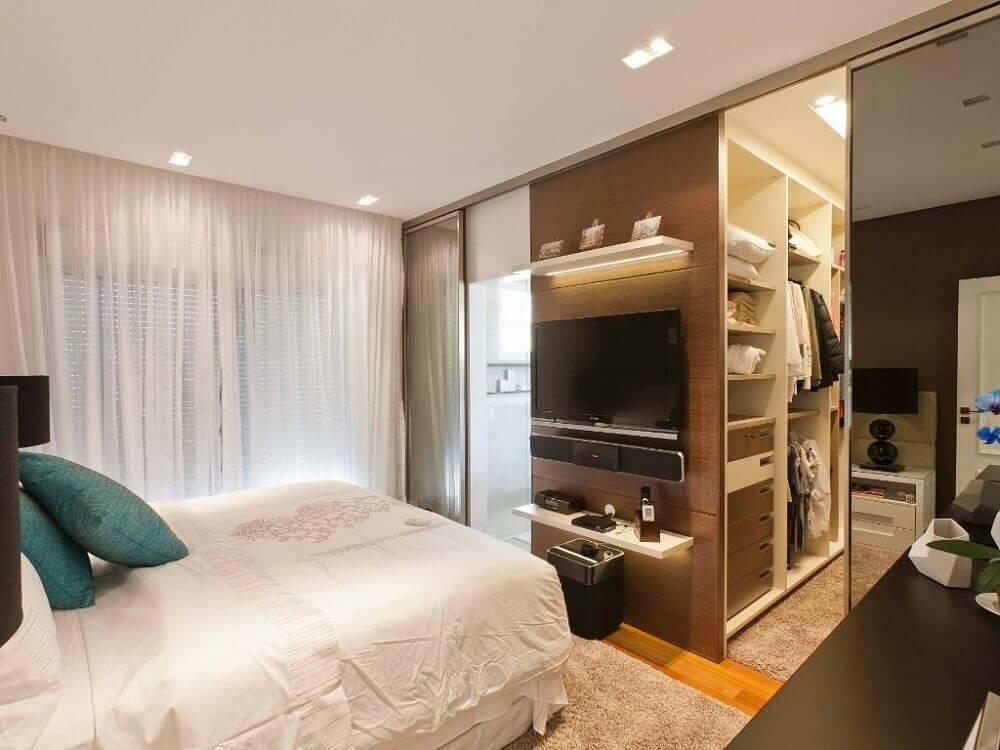 Quarto com closet e banheiro simples.