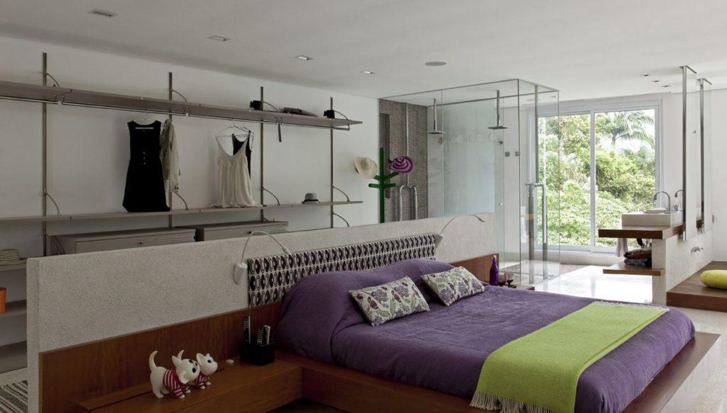 Quarto com closet aberto e banheiro  com parede de vidro.