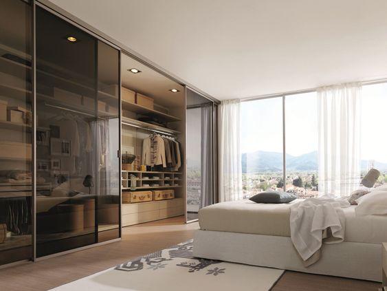 Quarto com closet com porta de vidro.