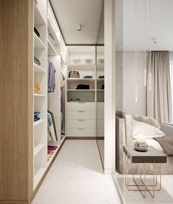 Quarto com closet com espelho grande e decoração clean.