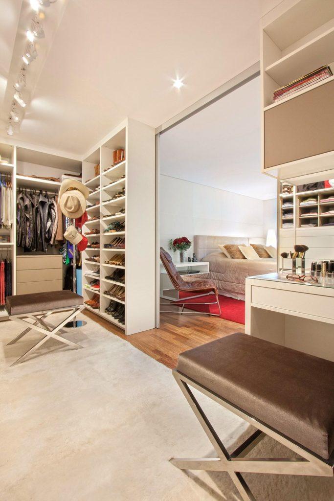 Quarto com closet com bancos e penteadeira.