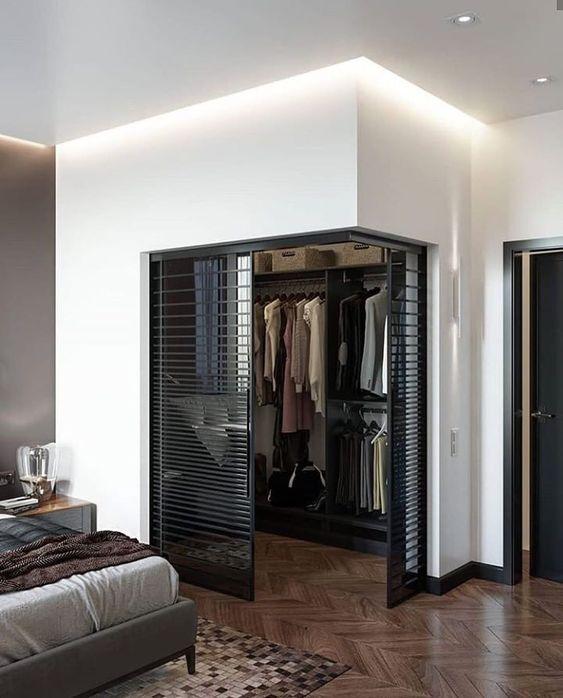 Quarto com closet com porta de vidro preta.
