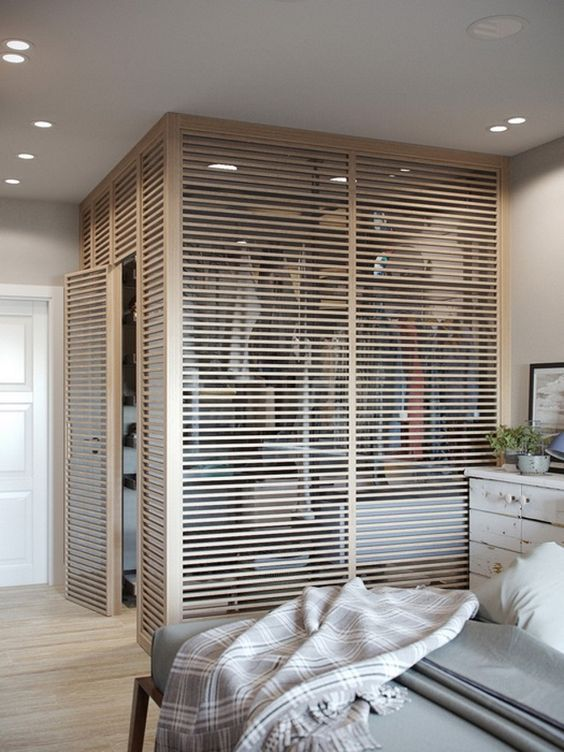 Quarto com closet com porta de madeira vazada.