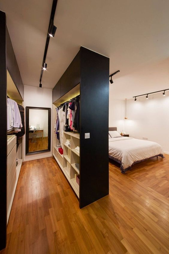 Quarto com closet moderno com trilho de iluminação.