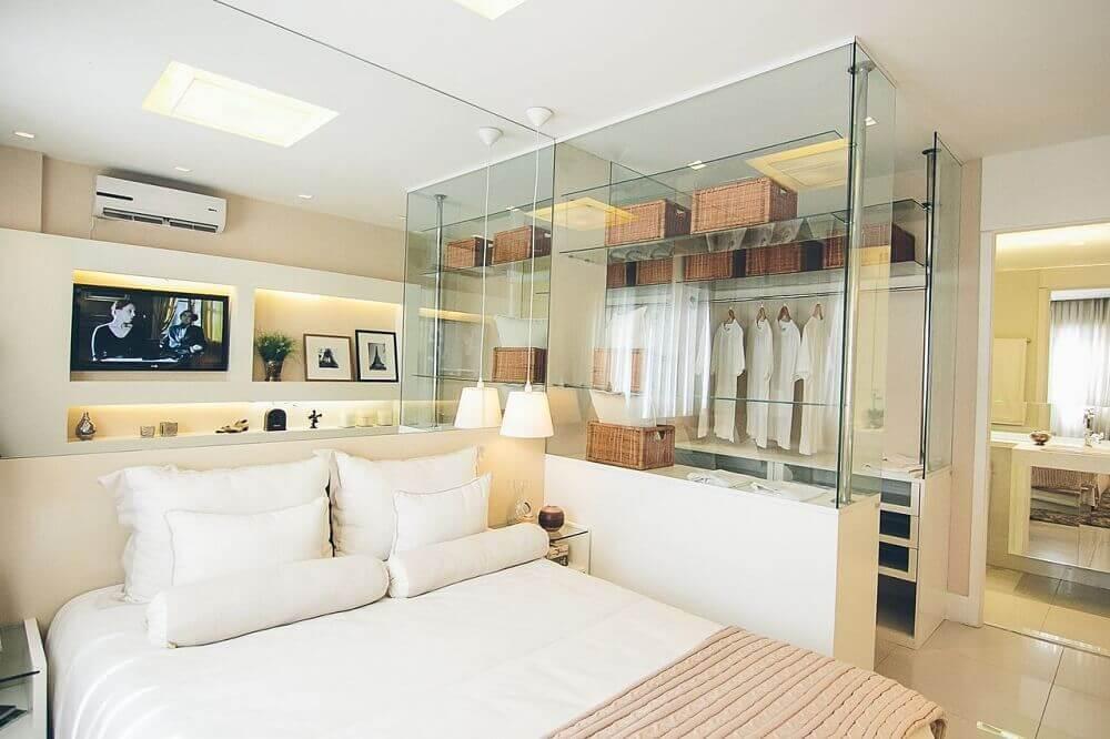 Quarto com closet com divisórias de vidro.