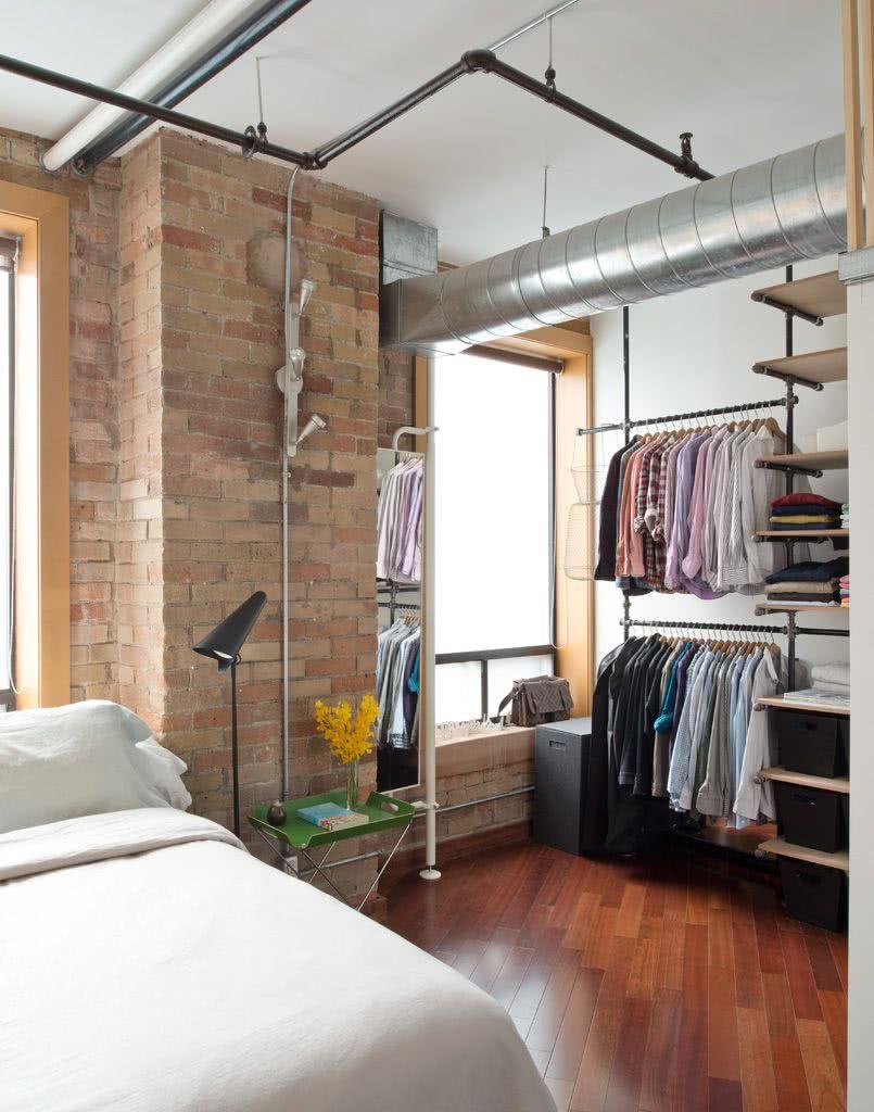 Quarto com closet aberto e decoração industrial.