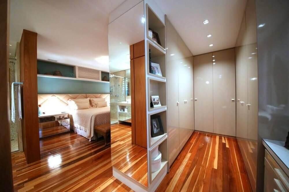 Decoração luxuosa com armários brancos e espelho.