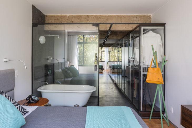 Decoração moderna com banheiro com divisória de vidro e armário espaçoso.