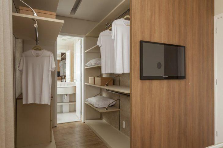 Decoração com televisão fixa no armário de madeira.
