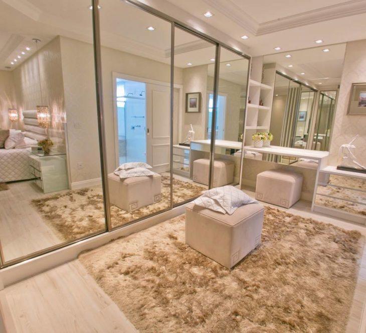 Closet luxuoso com portas espelhadas.