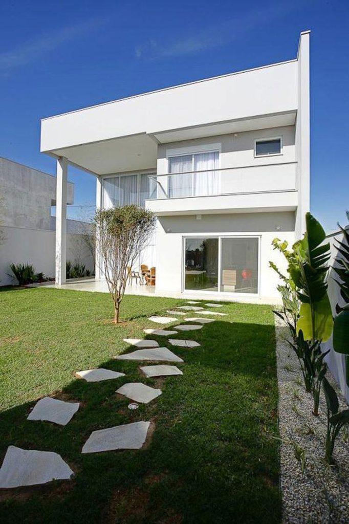 Casa branca com dois andares e projeto moderno.