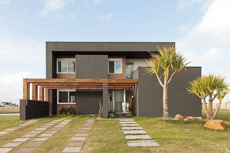 Casa moderna com revestimento cinza e pergolados.