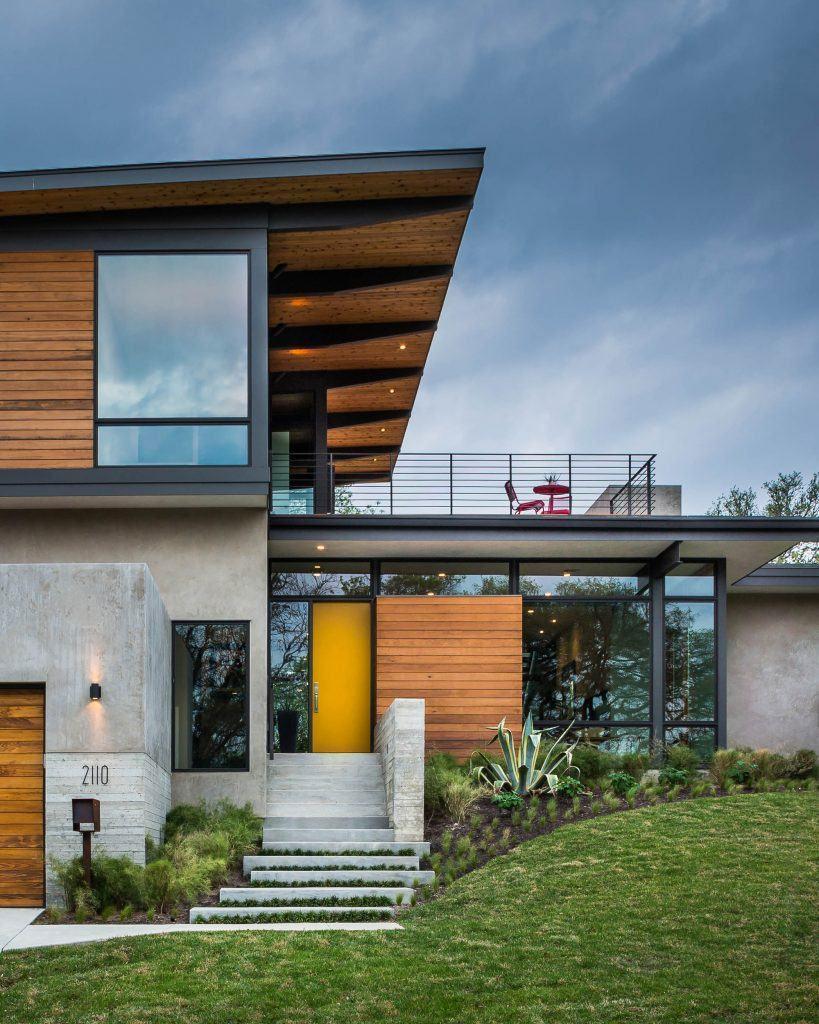 Casa moderna com revestimento de madeira e telhado embutido.