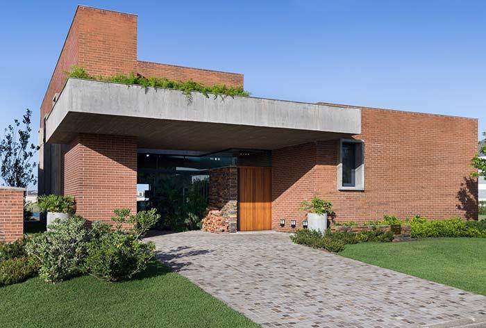 Casa térrea moderna com revestimento de plaqueta de cerâmica.