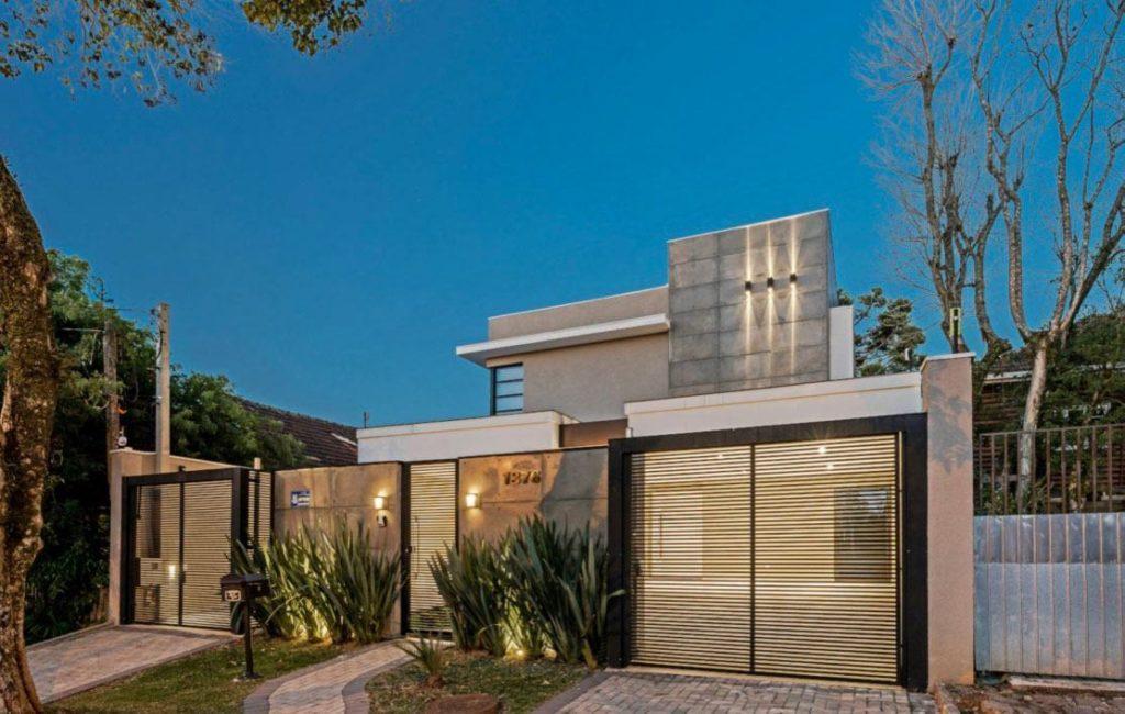 Casa moderna com telhado embutido e entrada para duas garagens.