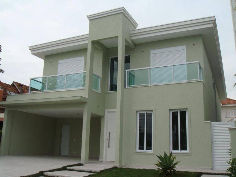 Casa verde com dois andares e telhado embutido.