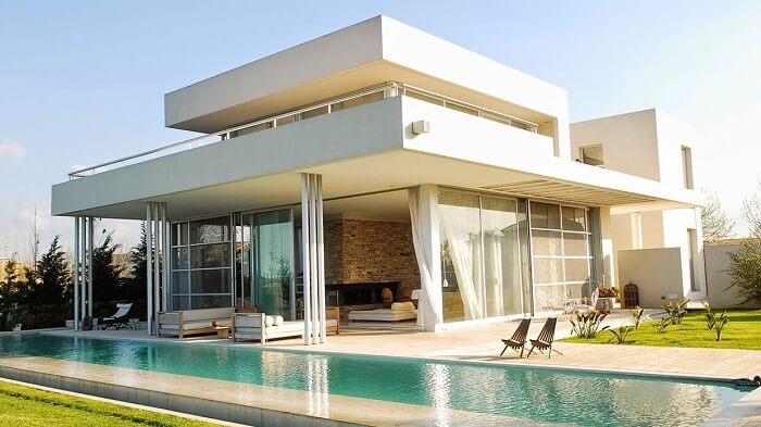 Construção moderna com paredes de vidro e piscina retangular.