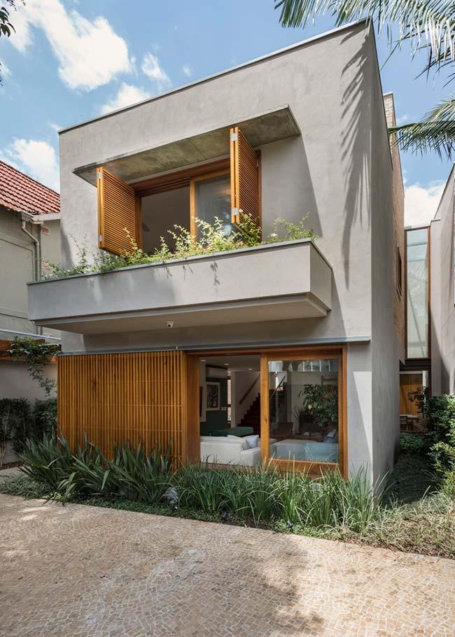 Fachada de sobrado moderno com janelas de madeira.