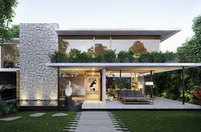 Fachada de casa moderna com dois andares com parede com revestimento de pedra.