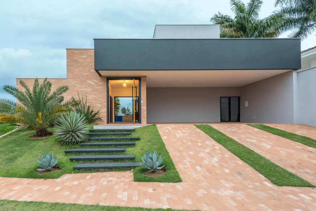Fachada de casa moderna e revestimento de tijolinho aparente.