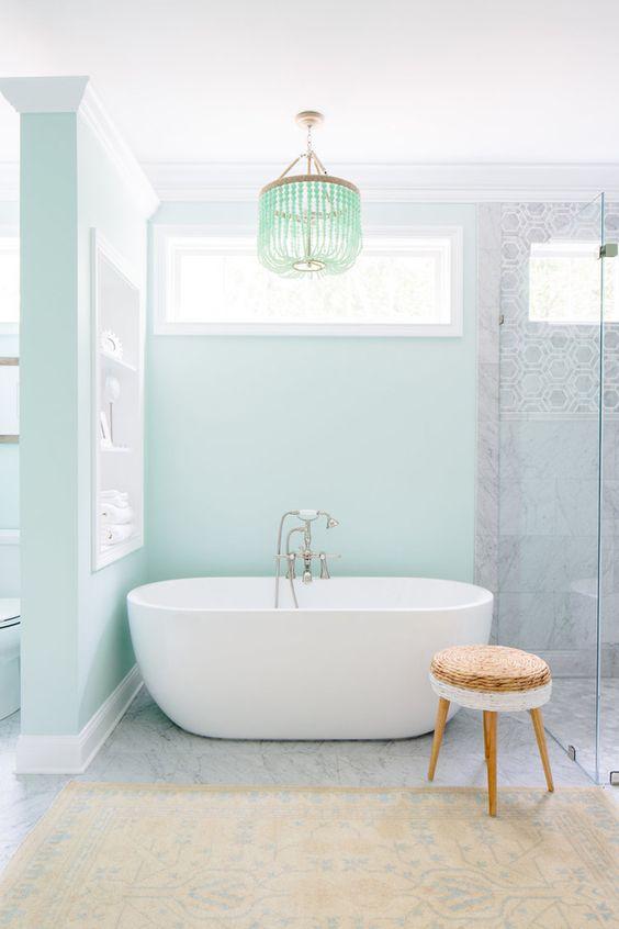 Banheiro feminino com banheiro e parede azul tiffany.