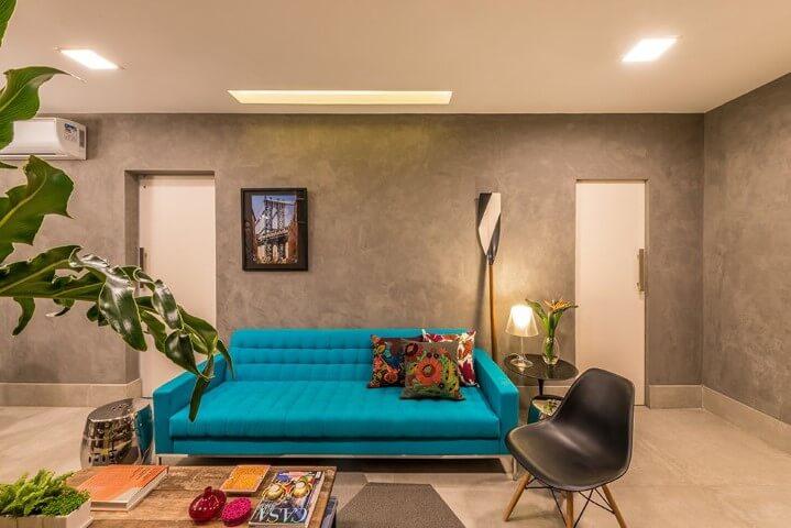 Sala moderna com parede de cimento queimado e sofá azul tiffany.